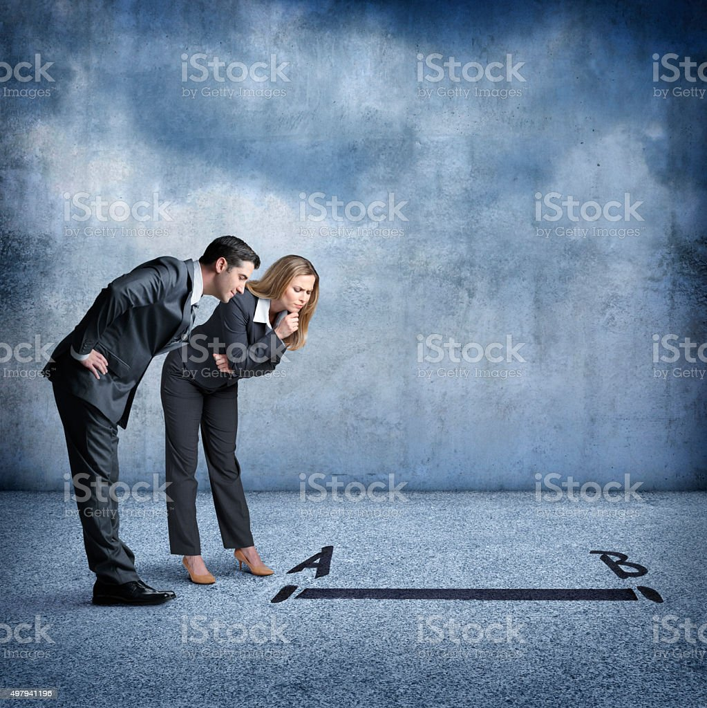 Businessman And Businesswoman Looking For Quickest Solution To Problem stock photo