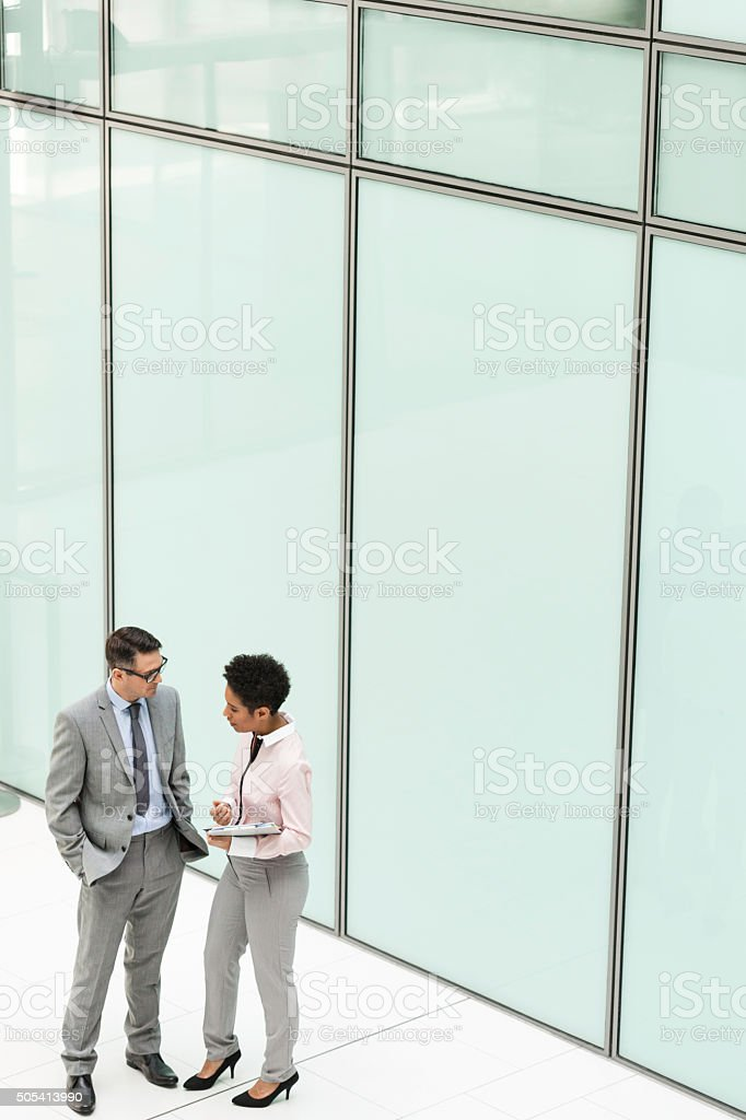 Businessman and businesswoman meet in office building. stock photo