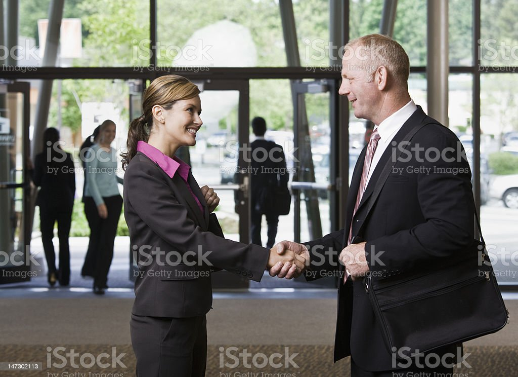 Businessman and Businesswoman Meeting in Lobby royalty-free stock photo