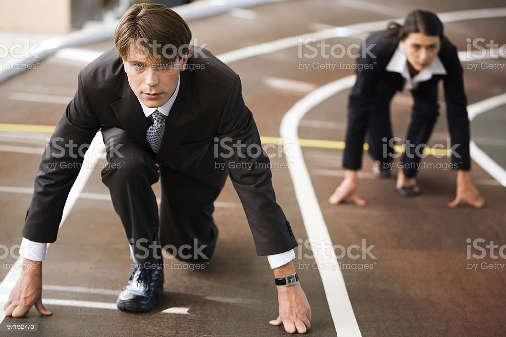 Businessman and businesswoman ready to race stock photo