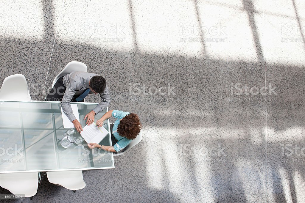 Businessman and businesswoman reviewing paperwork royalty-free stock photo