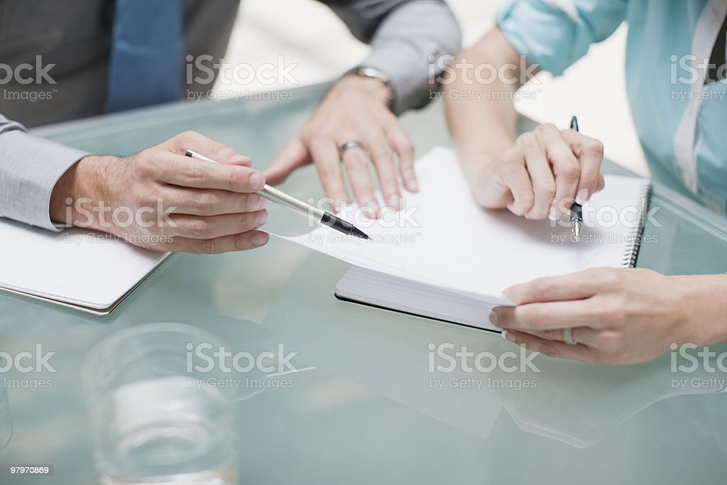 Businessman and businesswoman reviewing paperwork stock photo