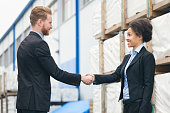 Businessman and businesswoman shaking hands and smiling