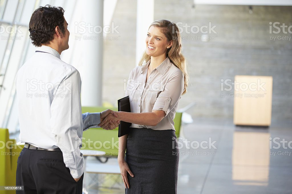 Businessman And Businesswoman Shaking Hands In Office stock photo