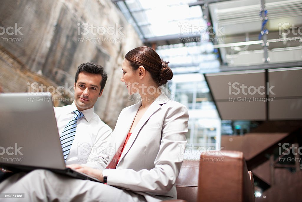 Businessman and businesswoman sharing laptop on lobby sofa royalty-free stock photo
