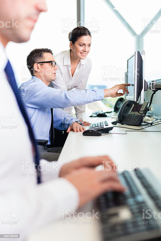 Businessman and businesswoman sharing results on screen. stock photo