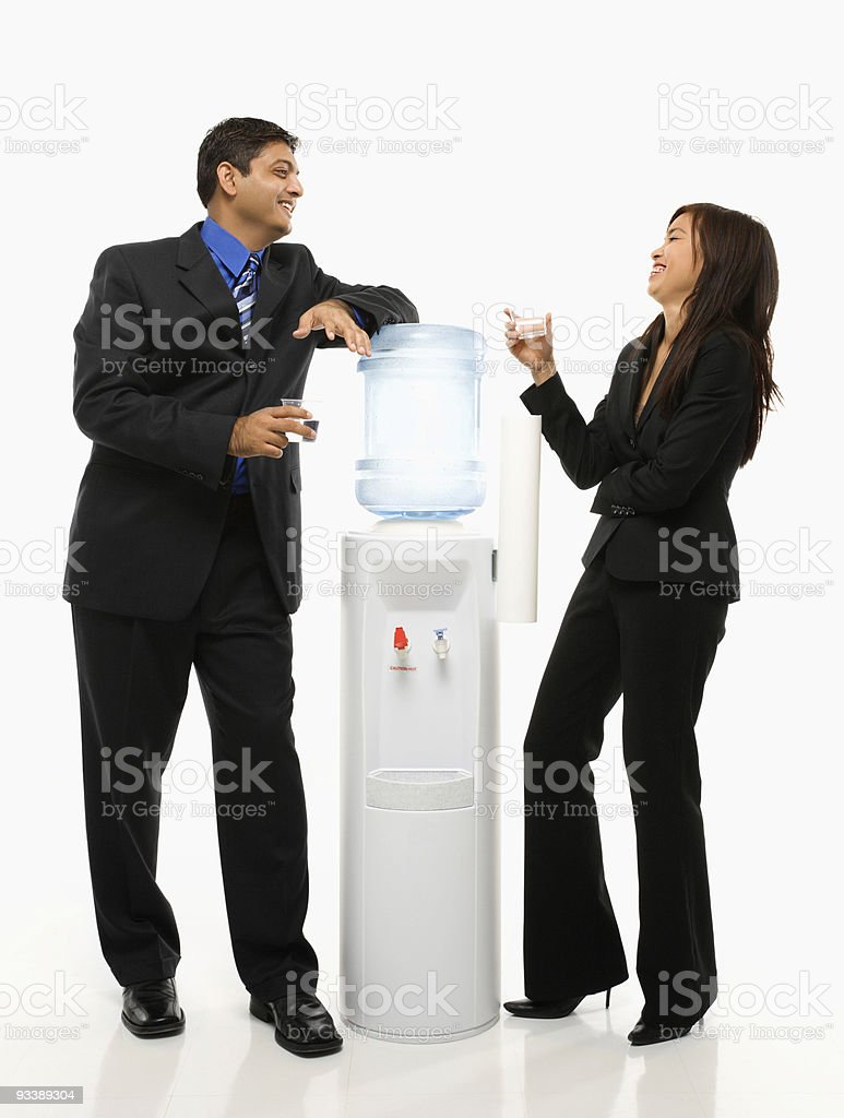 Businessman and businesswoman standing at water cooler. stock photo