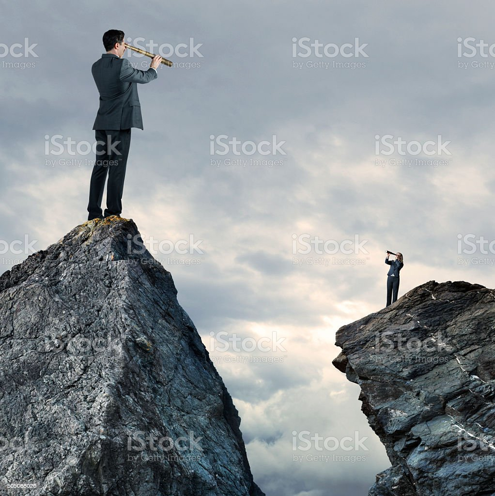 Businessman and Businesswoman Standing On Mountaintops Looking Through Spyglass stock photo