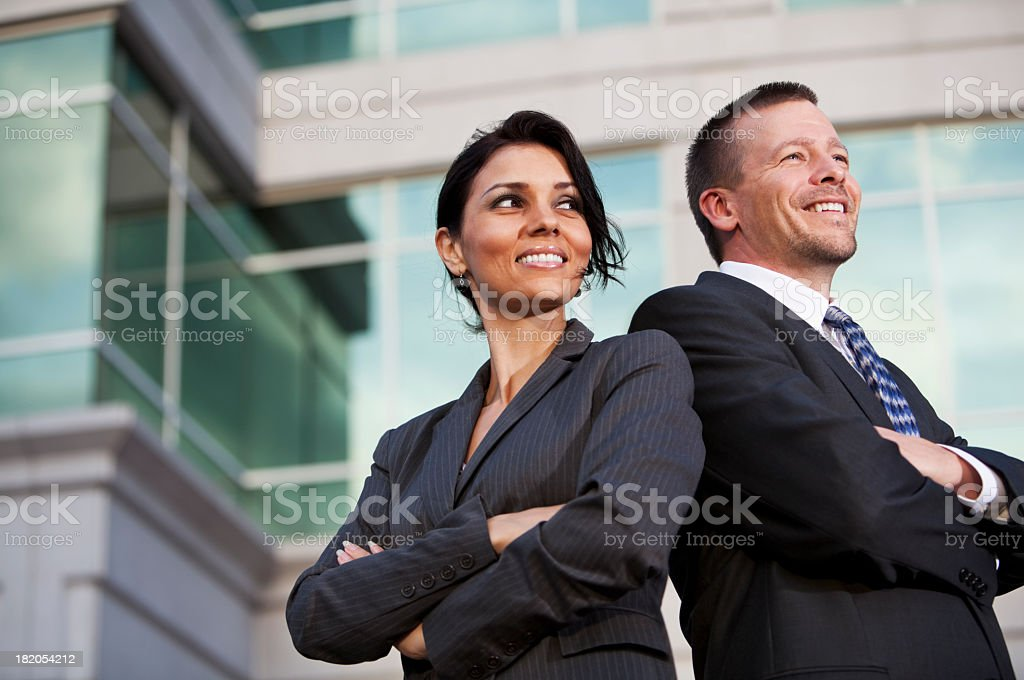 Businessman and businesswoman standing outside office building royalty-free stock photo
