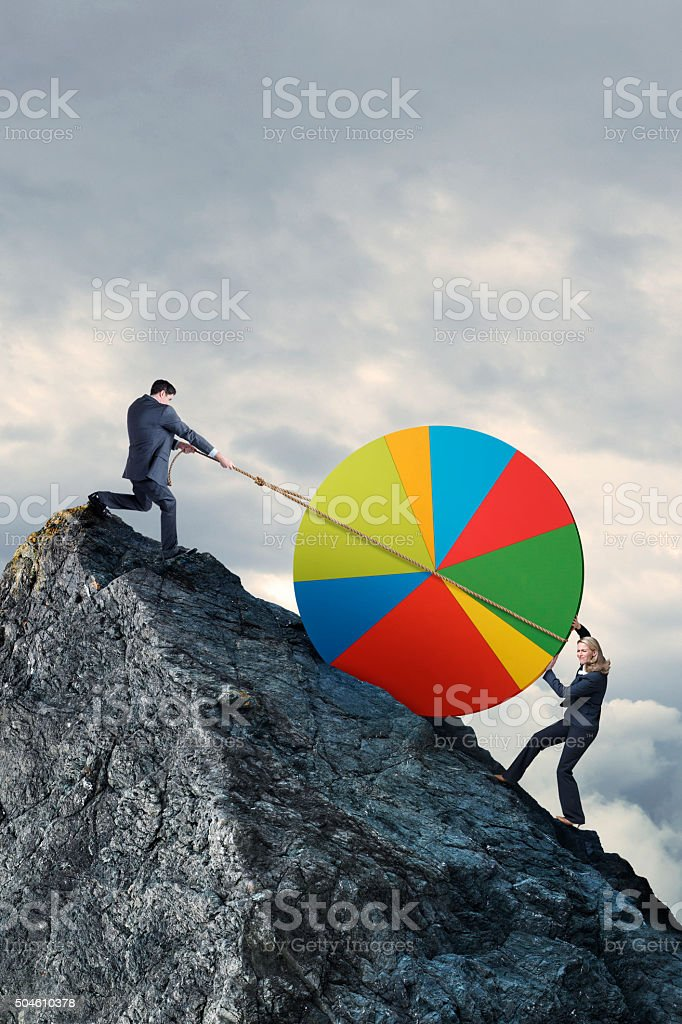 Businessman And Businesswoman Struggle To Lift Pie Chart To Montaintop stock photo