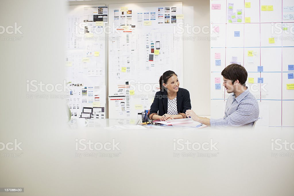 Businessman and businesswoman talking in meeting stock photo