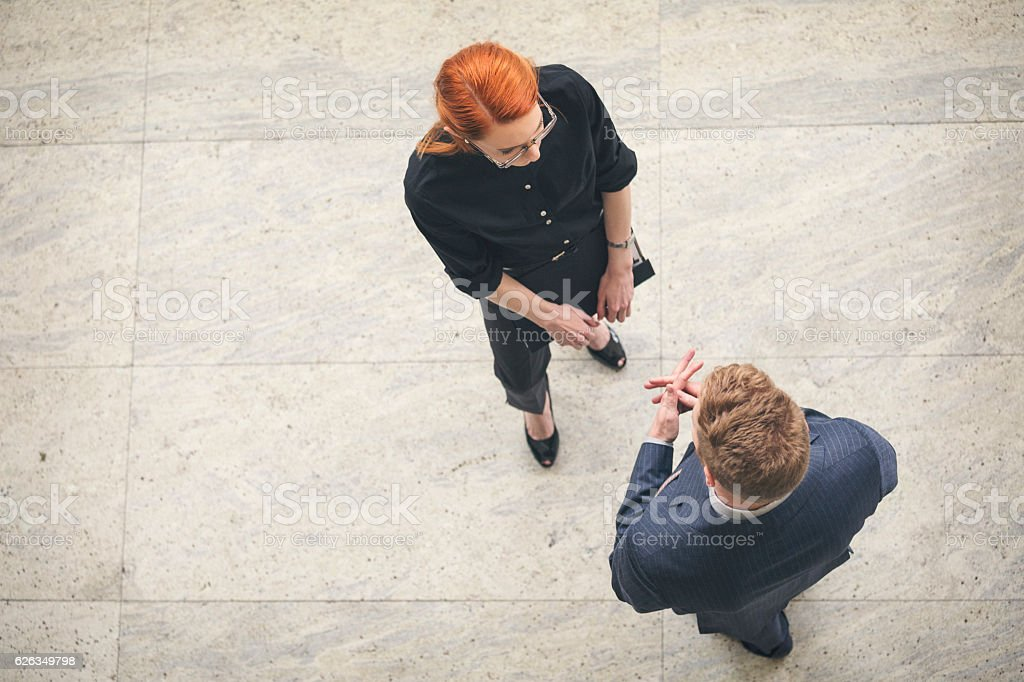 Businessman and businesswoman talking in the lobby overhead shot stock photo