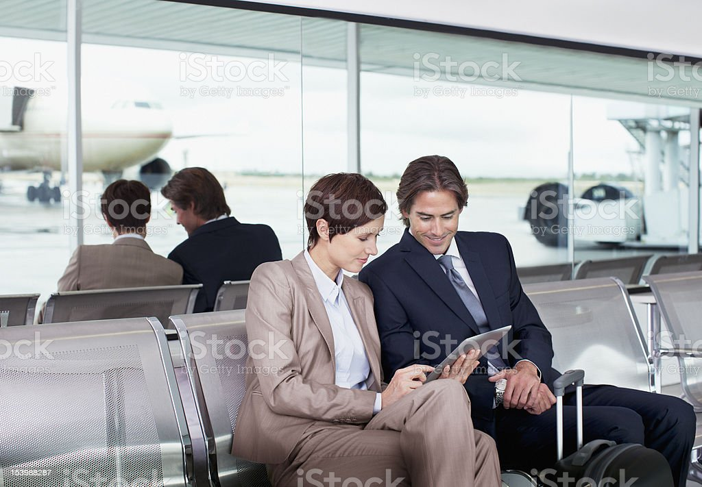 Businessman and businesswoman using digital tablet in airport royalty-free stock photo