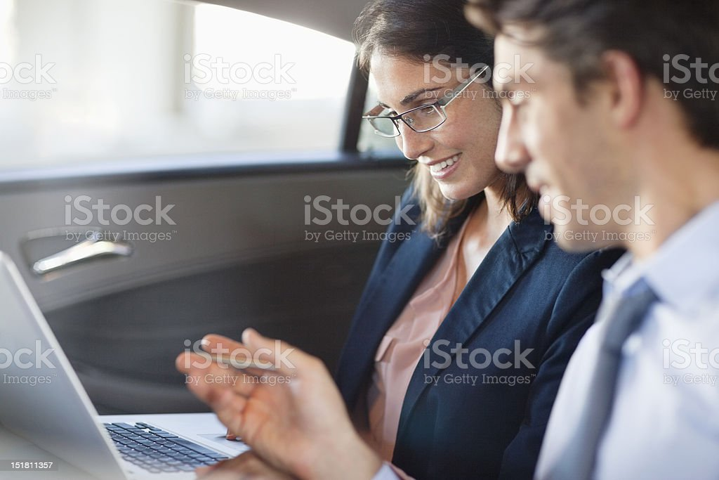 Businessman and businesswoman using laptop in back seat of car stock photo