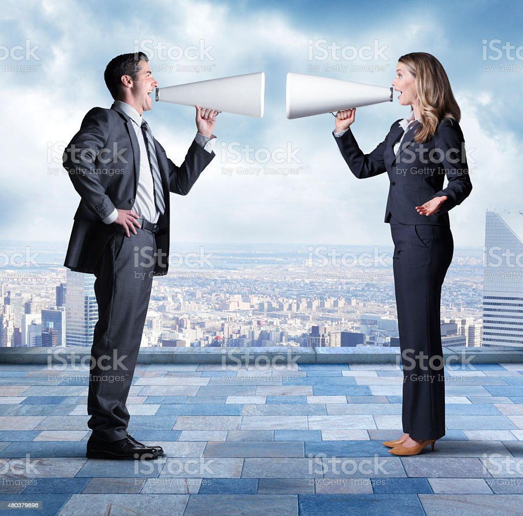 Businessman And Businesswoman Using Megaphones To Shout At Each Other stock photo