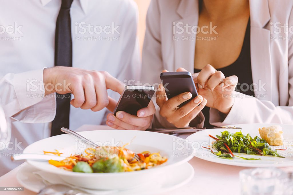 Businessman and businesswoman using smart phones at lunch stock photo
