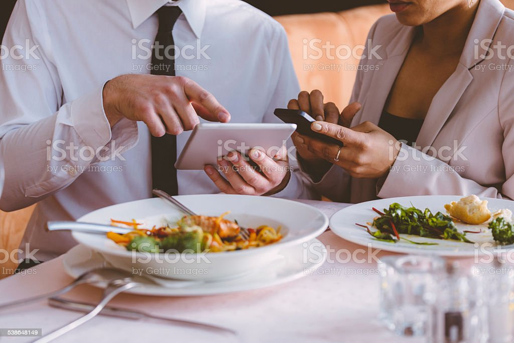 Businessman and businesswoman using technologies on lunch stock photo