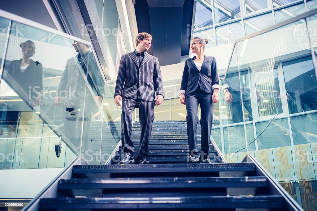 Businessman and businesswoman walking down the stairs and talking stock photo