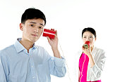 Businessman and Businesswoman with tin can phone