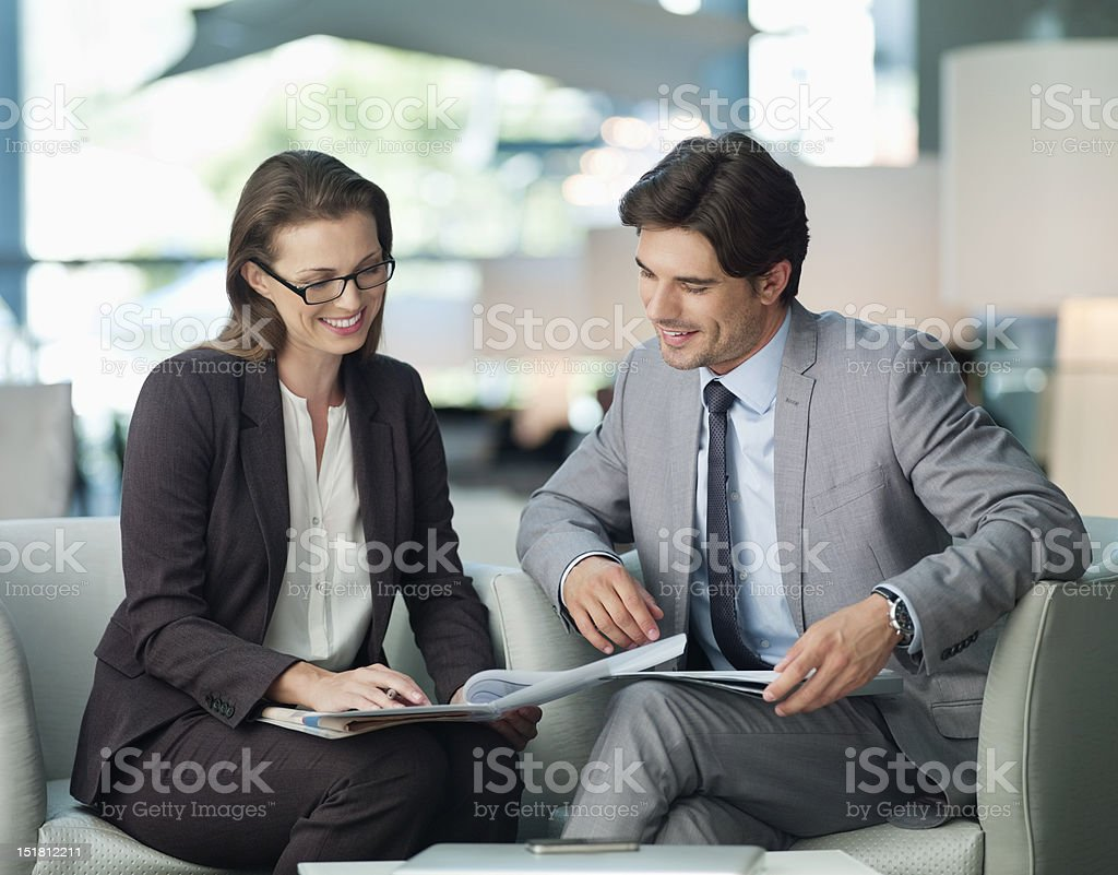 Businessman and businesswoman working in lobby royalty-free stock photo