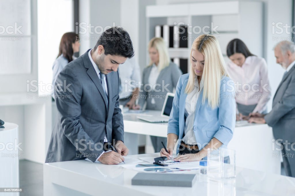 Businessman and businesswoman working in office together stock photo