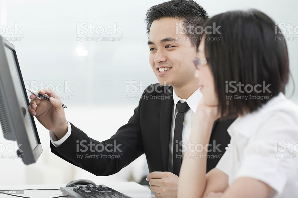 Businessman and businesswoman working on a computer royalty-free stock photo
