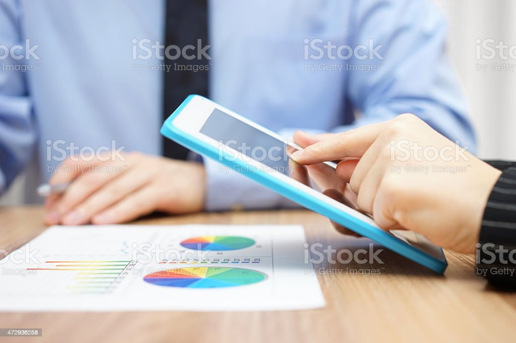 businessman and businesswoman working with tablet and paper report stock photo