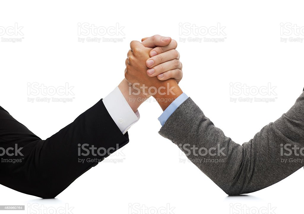 businessman and businesswoman wrestling on table stock photo