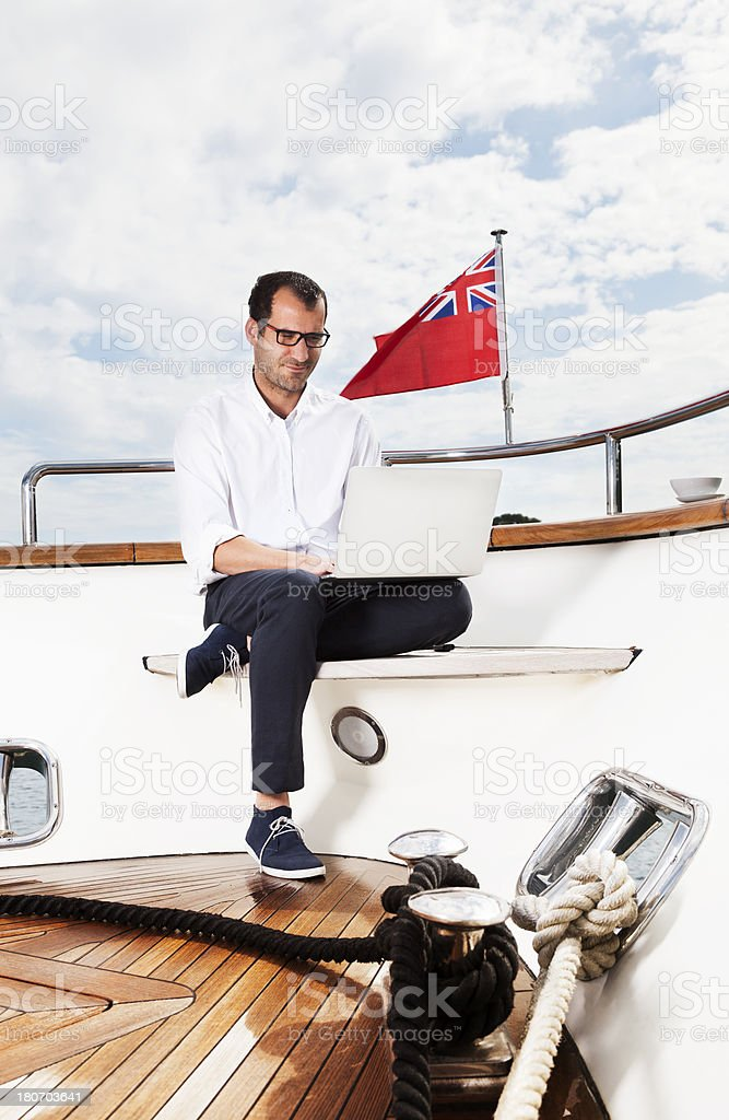 Businessman and Captain of the yacht relaxing. Reading e-mails. royalty-free stock photo