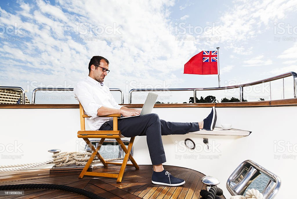 Businessman and Captain of the yacht relaxing. Reading e-mails stock photo