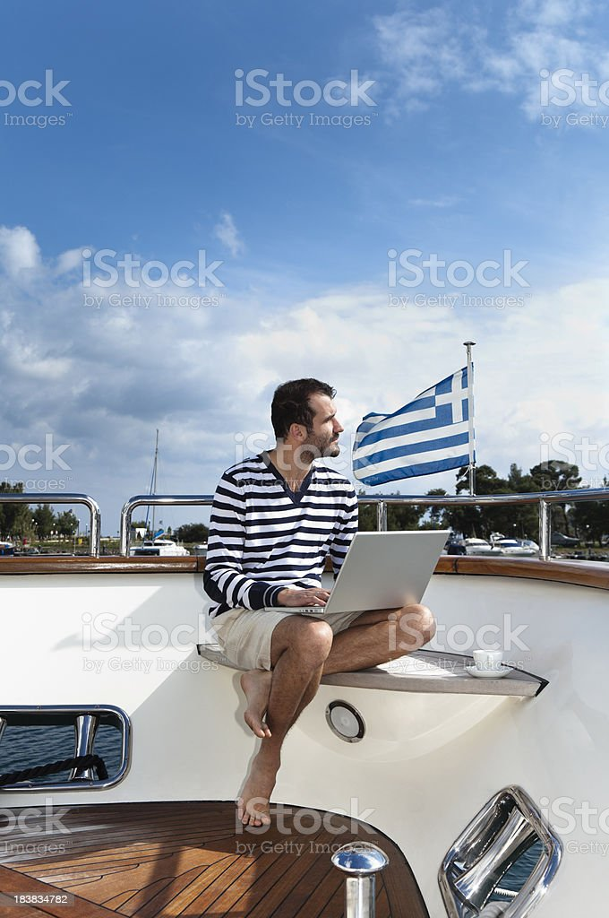 Businessman and Captain working on the laptop. Luxury yacht. royalty-free stock photo