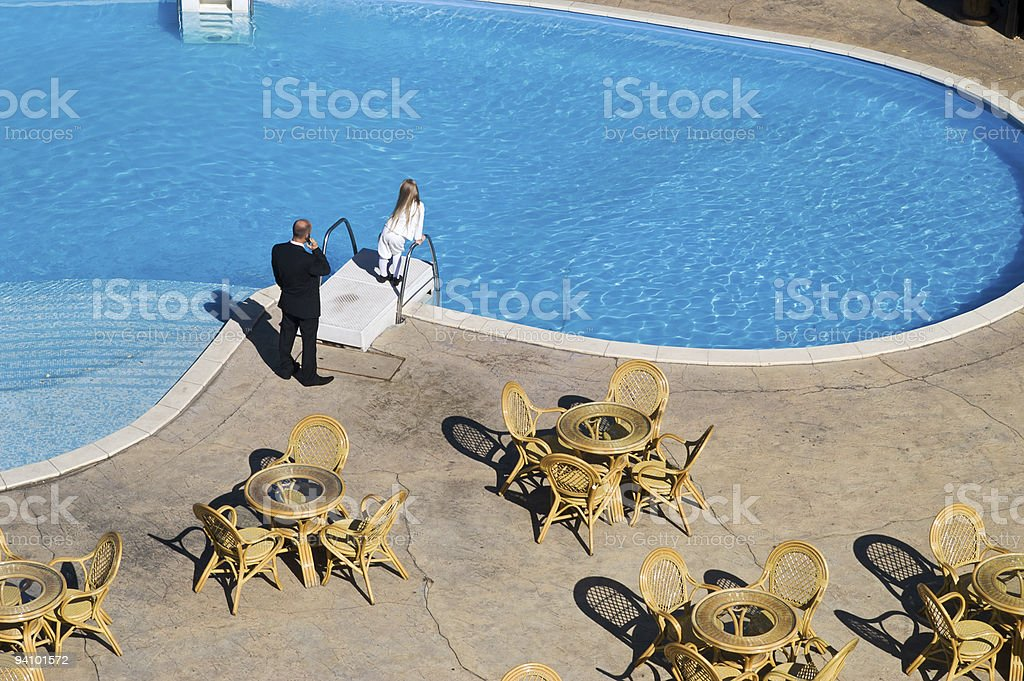 Businessman and child beside swimming pool stock photo