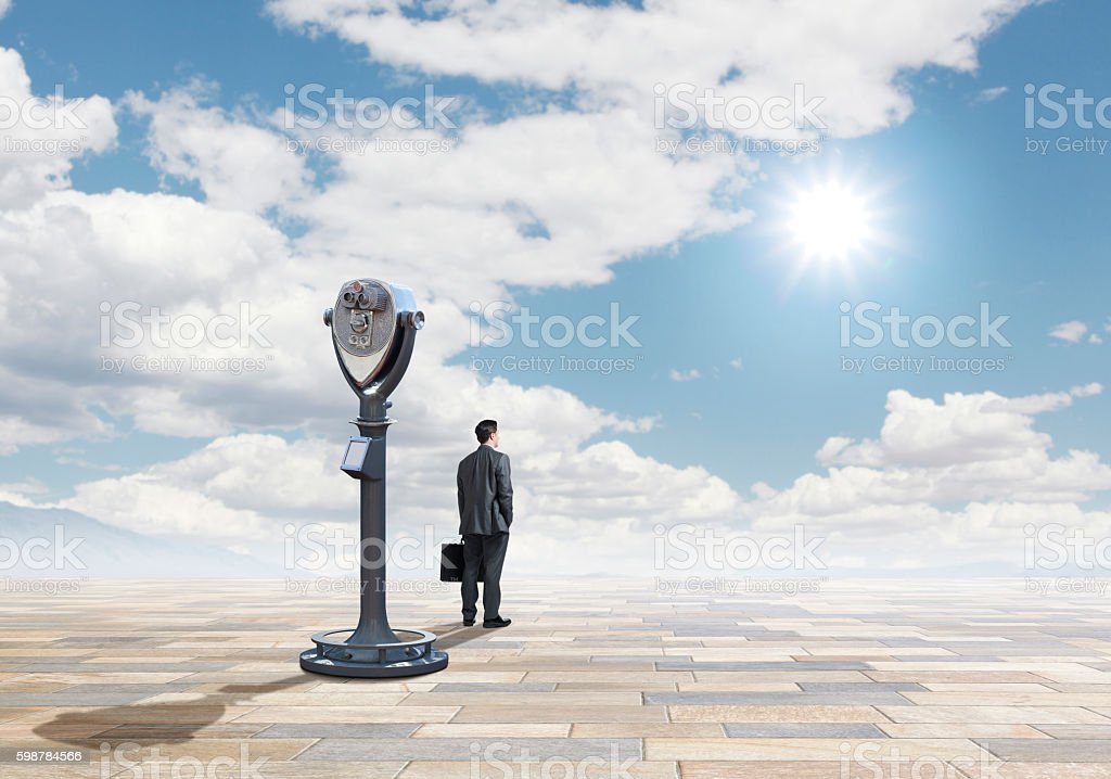 Businessman And Coin Operated Telescope With Sunburst In The Sky stock photo
