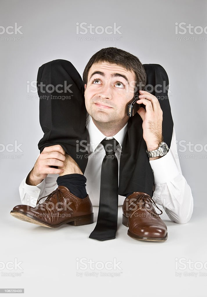 A businessman and contortionist in a suit on the phone stock photo