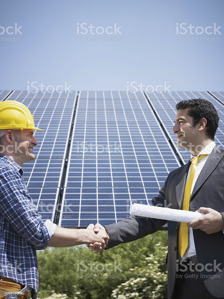 businessman and electrician shaking hands royalty-free stock photo