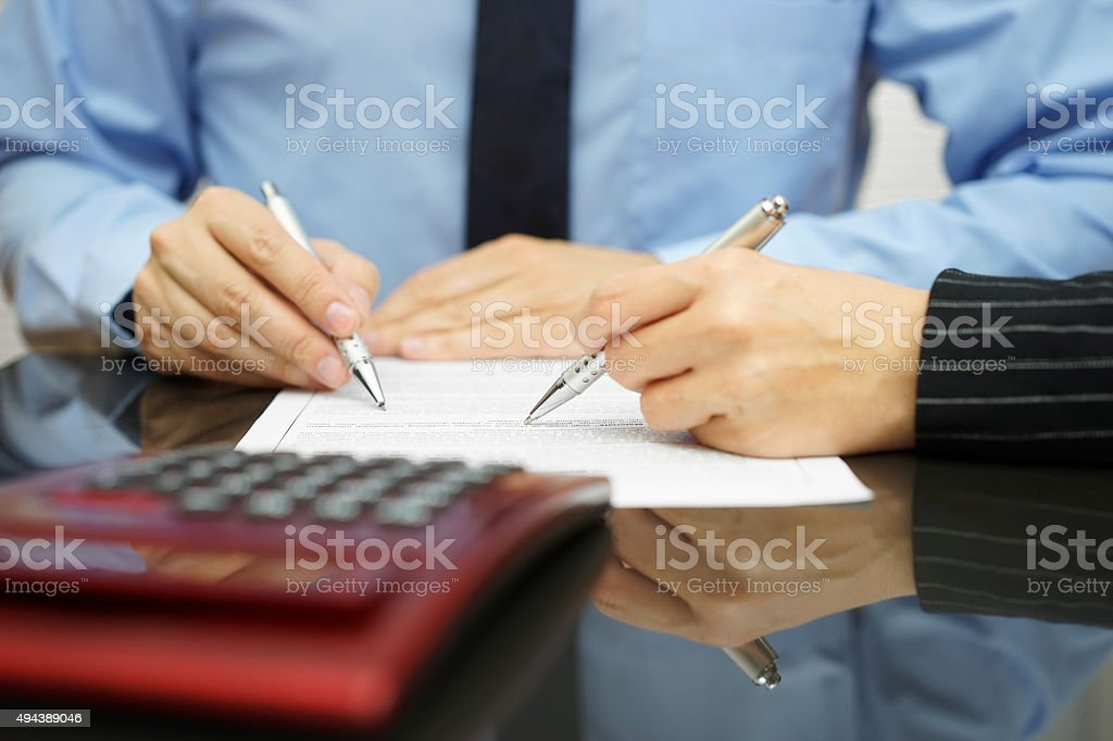 businessman and female coworker are examining financial agreement stock photo