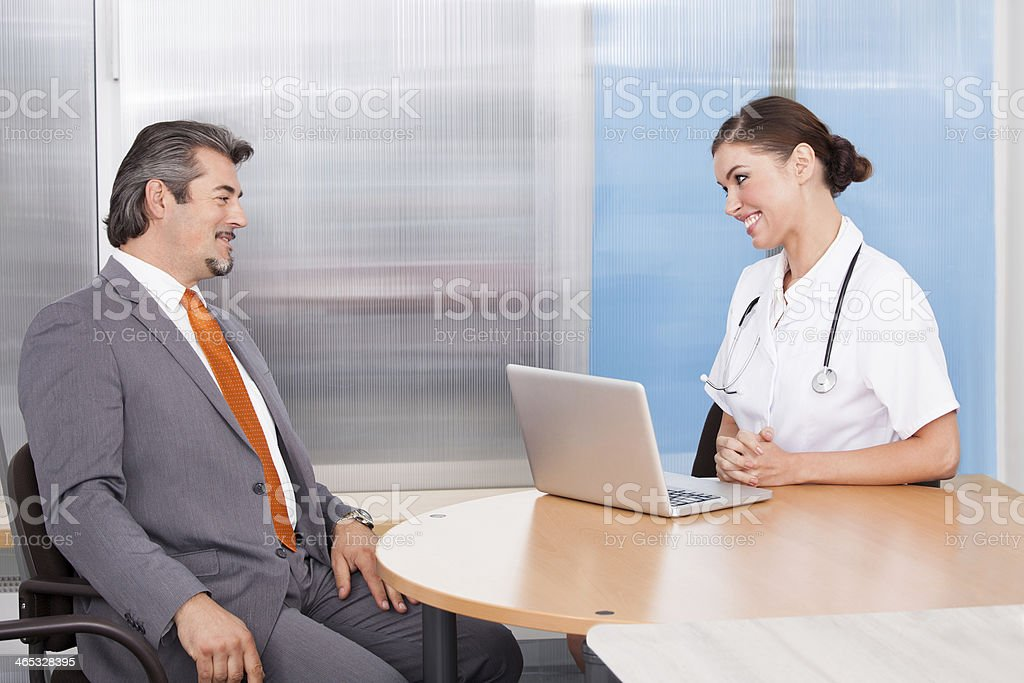 Businessman And Female Doctor Talking Together stock photo