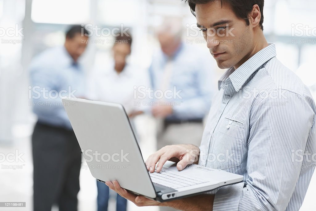 Businessman and laptop with coworkers at the back royalty-free stock photo