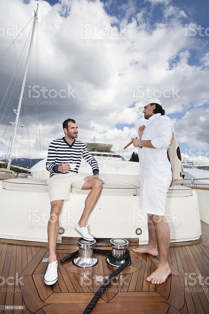 Businessman and sailor on board of the yacht stock photo
