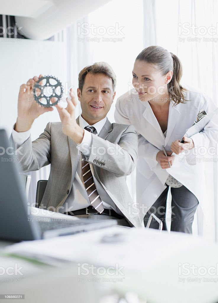Businessman and scientist looking at cog royalty-free stock photo