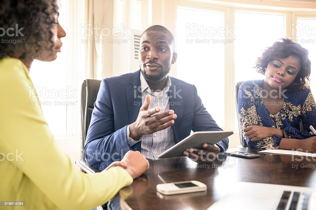 Businessman and two female colleagues in meeting stock photo