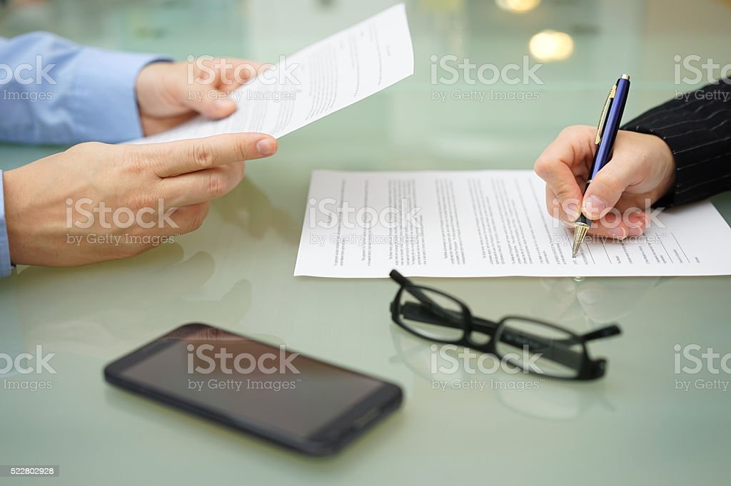 businessman and woman are reading and signing contract stock photo