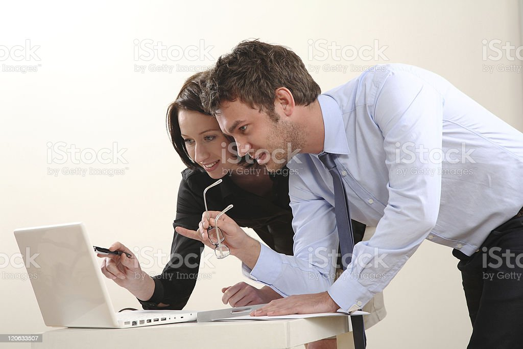 Businessman and woman discuss information on laptop screen stock photo