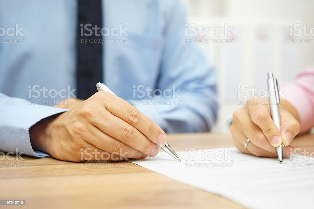 Businessman and woman hand signing agreement in office stock photo