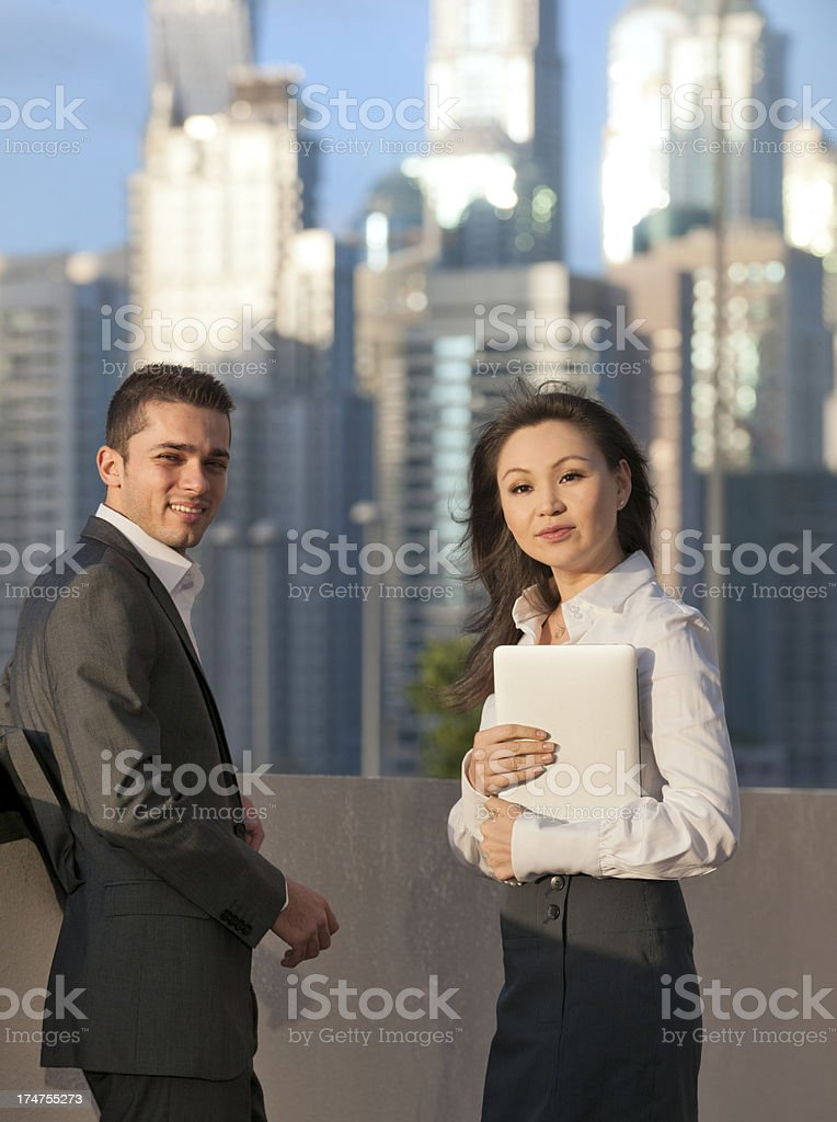 businessman and woman holding laptop in Dubai royalty-free stock photo