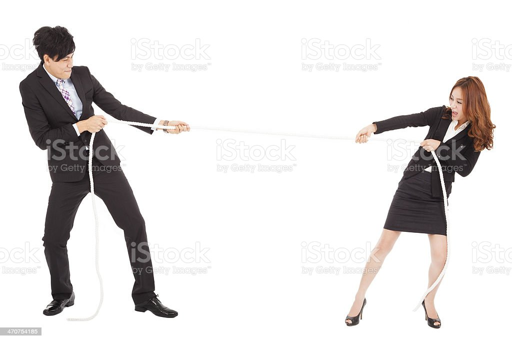 businessman and woman playing tug of  war stock photo