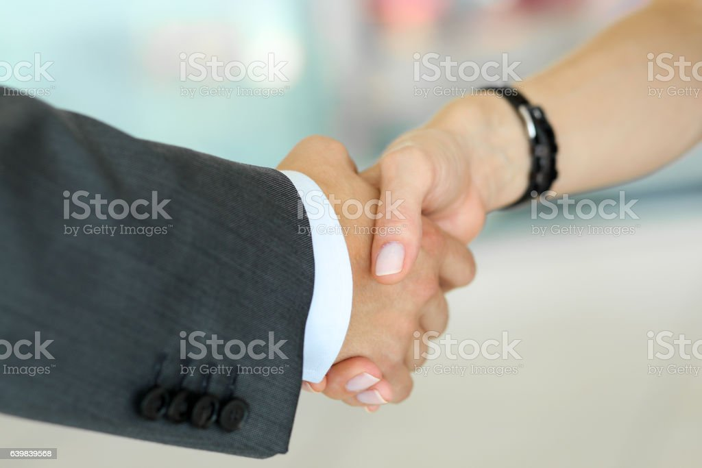 Businessman and woman shake hands as hello in office closeup stock photo