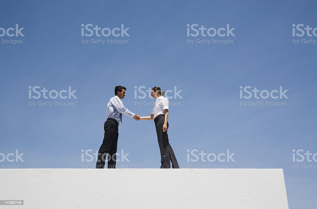 Businessman and woman shaking hands on wall outdoors with blue sky royalty-free stock photo