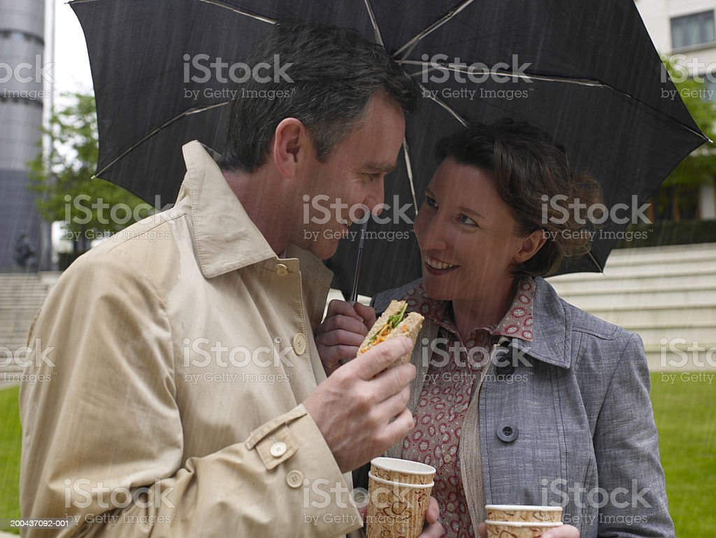 Businessman and woman sharing umbrella while having lunch, smiling royalty-free stock photo