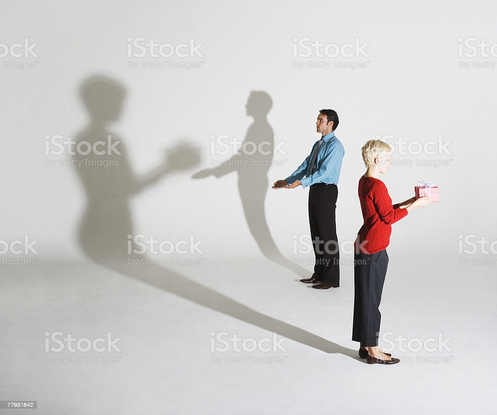 Businessman and woman standing so shadows look like she's giving him a gift royalty-free stock photo